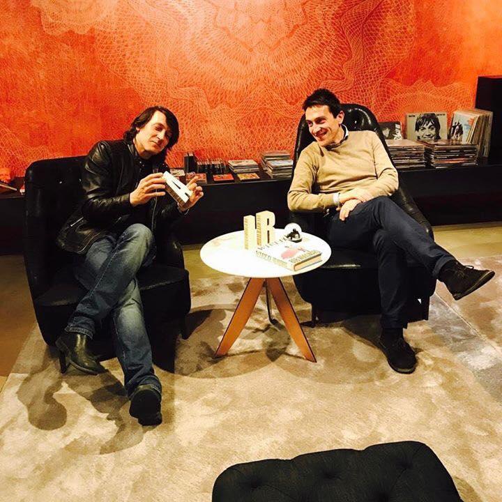 due persone sedute con tavolino con in mano un oggetto