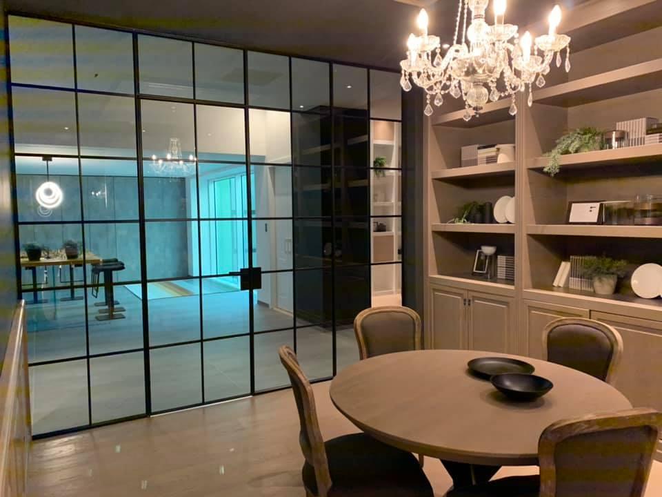 ambiente con tavoli sedie librerie e vetrata