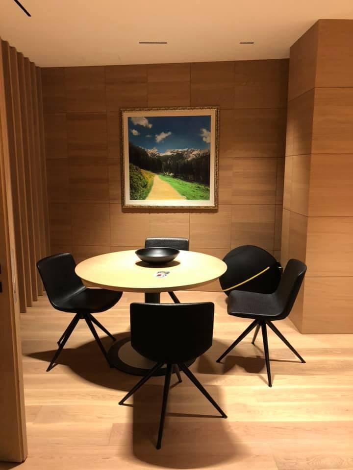 studio con tavolo e sedie e ambiente con pareti e pavimento rivestito di legno con quadro appeso
